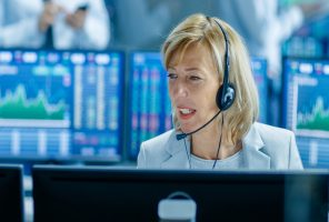 Chief Sales Force Representative Talks into the Headset. Behind Her People Working, Screens Show Stock Market Ticker Numbers and Graphs.