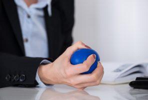 Businessperson Squeezing Stressball In Hand