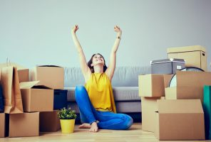 Happy young woman moving to new home – having fun