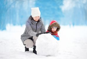 Little boy with his mother/babysitter/grandmother building snowman in snowy park