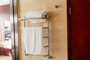 Modern heated towel rail on tiled bathroom wall.