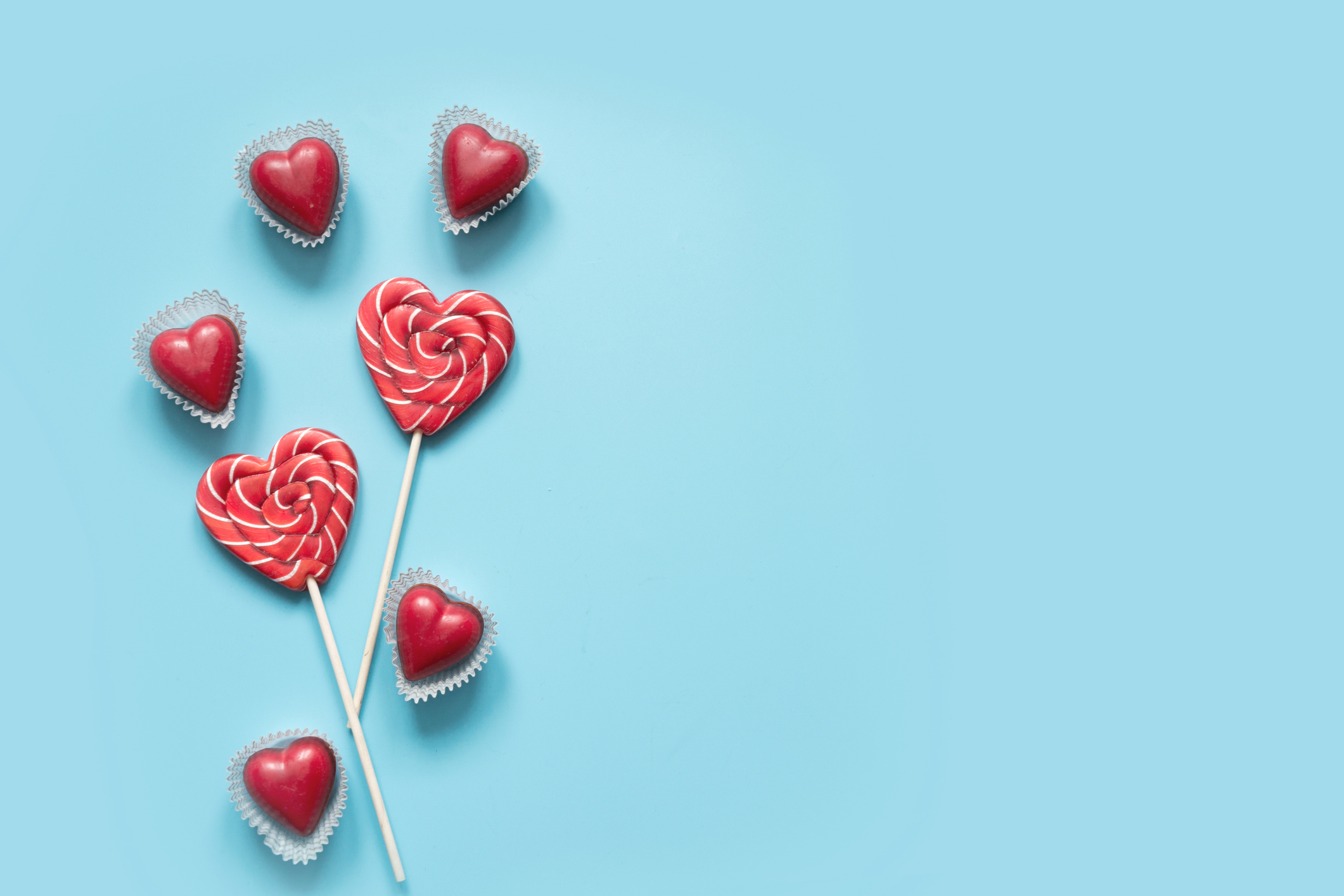 Valentine's card. Lollipops candy as heart on blue. Funny concept.