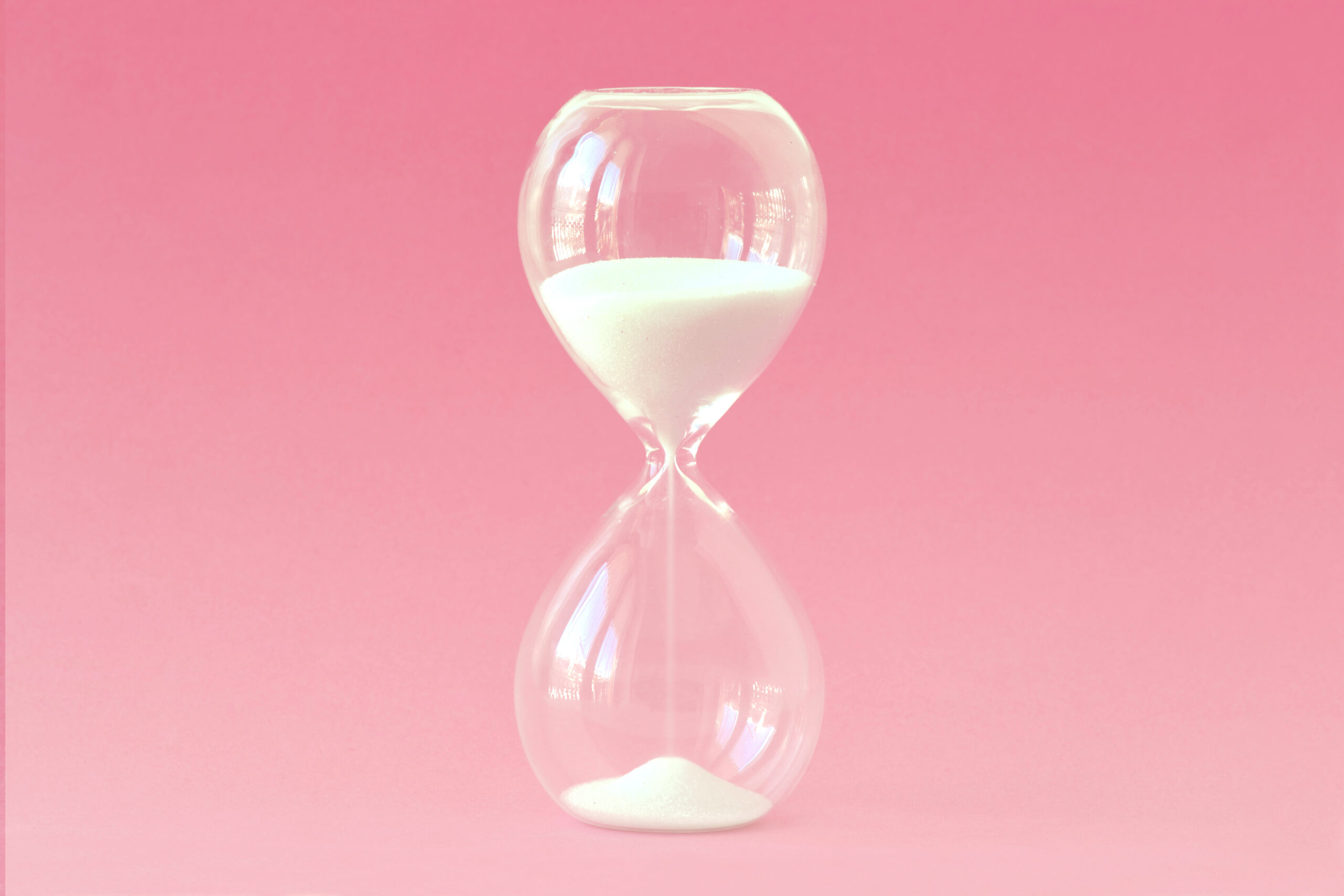 Hourglass on pink background – Concept of health, fertility and biological clock in women