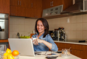 Cheerful woman enjoying morning routine while working on laptop in kitchen