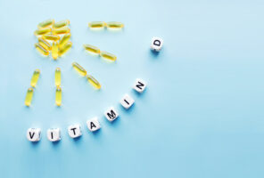 Yellow capsules in the form of the sun with rays and the word vitamin D from white cubes